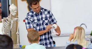 Vista delantera del profesor de sexo masculino caucásico que explica el modelo en la sala de clase 4k metrajes