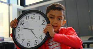 Vista delantera del reloj de pared asiático de la tenencia del colegial en el escritorio en sala de clase en la escuela 4k almacen de metraje de vídeo
