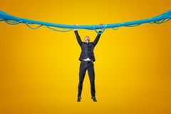 Vista delantera integral del hombre de negocios que cuelga que agarra por el hilo pegajoso azul del limo en el fondo ambarino fotografía de archivo