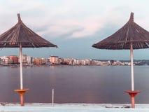Vista delantera para varar los paraguas de la paja y la línea de la playa arenosa albania fotos de archivo libres de regalías