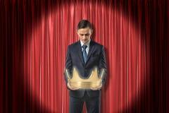 vista delantera Rodilla-profunda del hombre de negocios que mira abajo la corona del oro que ?l est? sosteniendo en manos, la cor fotografía de archivo libre de regalías