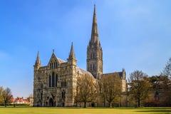 Vista delantera y parque el día soleado, Inglés del sur de la catedral de Salisbury Fotografía de archivo