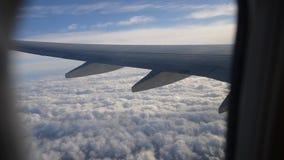 vista dell'ala dell'aeroplano attraverso la finestra piana Volando sopra le nubi stock footage