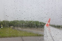 Vista dell'ala dell'aereo attraverso la finestra bagnata dalla pioggia (carta da parati vaga) Fotografia Stock