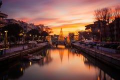 Vista dell'albero di Natale su un ponte al tramonto, con le nuvole arancio Immagine lunga di esposizione in Riccione, Emilia Roma fotografia stock libera da diritti