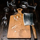 Vista dell'angolo alto dei bicchieri di vino e dell'ascia rotti con il bordo di legno Fotografia Stock Libera da Diritti