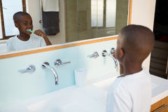 Vista dell'angolo alto dei denti di spazzolatura del ragazzo veduti dalla riflessione di specchio immagine stock