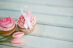 Vista dell'angolo alto dei nastri di rosa di consapevolezza del cancro al seno sui bigné con i tulipani Immagine Stock