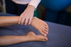 Vista dell'angolo alto dei piedi d'esame del terapista femminile con il ragazzo che si trova sul letto immagini stock