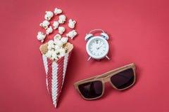 Vista dell'angolo alto del cono con gli occhiali del cinema e del popcorn con la piccola sveglia sul concetto minimalistic del fo Immagine Stock