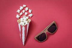 Vista dell'angolo alto del cono con gli occhiali del cinema e del popcorn sul concetto minimalistic del fondo rosso Immagine Stock Libera da Diritti