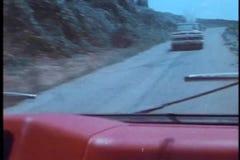 Vista dell'angolo alto del volante della polizia che insegue furgone rosso sulla strada campestre archivi video