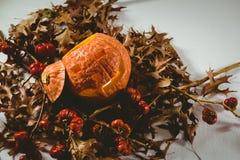 Vista dell'angolo alto della lanterna della presa o con le piccole zucche e foglie di autunno Immagine Stock