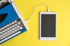 Vista dell'angolo alto della macchina da scrivere d'annata relativa alla compressa digitale su giallo fotografie stock