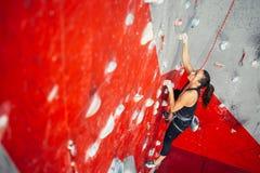 Vista dell'angolo alto della parete di pratica della donna che scala su un bordo della città universitaria Donna che scala su un  Fotografie Stock