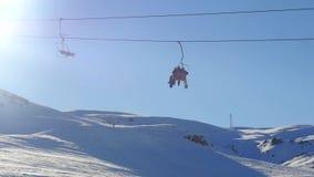Vista dell'ascensore di sci commovente con lo snowboard degli sportsmens e della gente dalla montagna nevosa su fondo stock footage