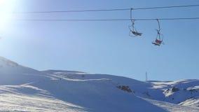 Vista dell'ascensore di sci commovente e dello snowboard allegro della gente dalla montagna nevosa su fondo video d archivio