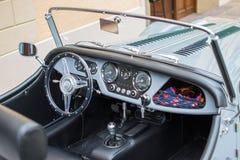 Vista dell'interno di un'automobile convertibile classica, con un volante metallico ed il cruscotto fotografia stock