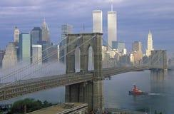 Vista dell'orizzonte di New York, del ponte di Brooklyn sopra il East River e del rimorchiatore in nebbia, NY Fotografia Stock