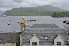 Vista della baia di Portree dal porto di Portree con i tetti di ardesia tradizionali nella priorità alta, isola di Skye, altopian Immagine Stock