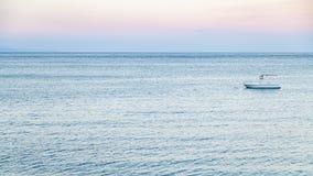 Vista della barca in mare ionico nella penombra di estate immagine stock libera da diritti