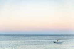 Vista della barca in mare ionico nella sera di estate fotografie stock
