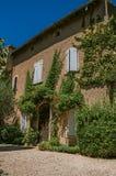 Vista della casa di pietra tipica che affronta un'iarda, con cielo blu ed i fiori soleggiati a Ménerbes Fotografia Stock
