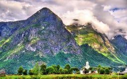 Vista della chiesa e delle montagne di legno bianche di Oppstryn in Norvegia Fotografia Stock Libera da Diritti