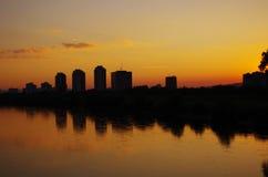Vista della città attraverso il fiume nella sera. immagine stock