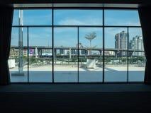 Vista della città dalla grande finestra nella costruzione di convenzione immagini stock libere da diritti