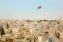 Vista della città di Amman con la grande bandiera della Giordania Immagini Stock Libere da Diritti