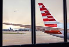 Vista della coda della fusoliera dell'aeroplano attraverso la finestra all'aeroporto fotografia stock