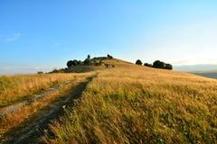 Vista della collina con la strada ed il cielo blu Fotografia Stock