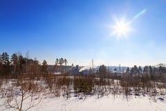 Vista della fabbrica con fumo dal bordo del tubo del giorno del sole di inverno della foresta Immagini Stock Libere da Diritti