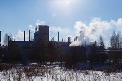 Vista della fabbrica con fumo dal bordo del tubo del giorno del sole di inverno della foresta Fotografie Stock Libere da Diritti