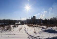 Vista della fabbrica con fumo dal bordo del tubo del giorno del sole di inverno della foresta Immagini Stock