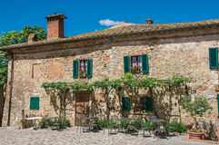 Vista della facciata di vecchia casa con i rampicanti nel villaggio di Monteriggioni Immagine Stock