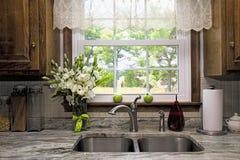 Vista della finestra della cucina con i fiori ed i pomodori del vaseof sul davanzale della finestra Fotografia Stock