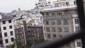 Vista della finestra sulle facciate di grandi nuove alte costruzione e chiesa bianche il giorno nuvoloso stock footage