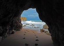 Vista della finestra sulle orme su una spiaggia sabbiosa che conduce alla s blu fotografia stock libera da diritti