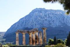 Vista della fortezza Acrocorinth da Corinto antico, Grecia con le colonne del tempio di Apollo nella priorità alta Fotografia Stock Libera da Diritti