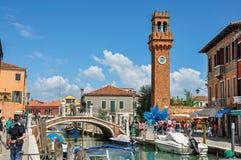 Vista della gente, delle costruzioni e della torre di orologio davanti al canale a Murano Fotografia Stock Libera da Diritti