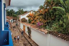 Vista della gente in vicolo con il marciapiede di pietra e di vecchie case in Paraty Fotografia Stock