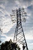 Vista della linea elettrica contro le nuvole di cielo blu alla luce solare fotografia stock libera da diritti
