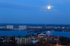 Vista della luna in anticipo in cielo blu di sera con la riflessione nel fiume cityscape Fotografia Stock