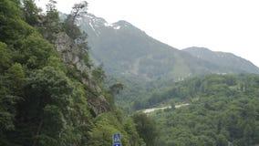 Vista della montagna con i picchi della neve e della foresta in primavera stock footage