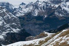 Vista della montagna e del villaggio della neve alle alpi Fotografia Stock