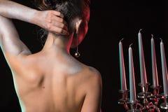 Vista della parte posteriore di una donna con bodyart d'argento e l'acconciatura piacevole che tengono candeliere con cinque cand Fotografia Stock
