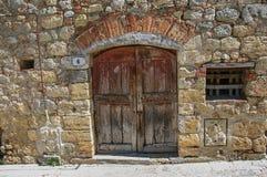 Vista della porta di legno in una parete di pietra nel villaggio di Monteriggioni Fotografia Stock