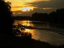 Vista della riva del fiume con il tramonto ed il crogiolo di a lungo coda Fotografia Stock